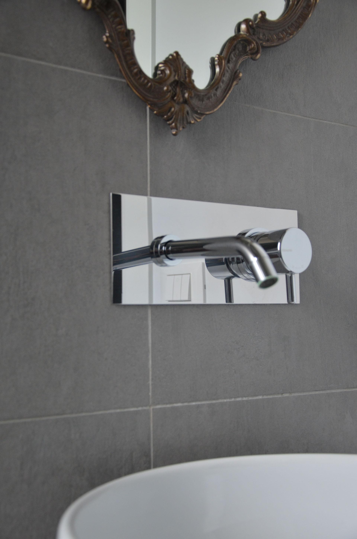 casa MG EG. particolare del rubinetto a parete e specchio di recupero nel bagno principale