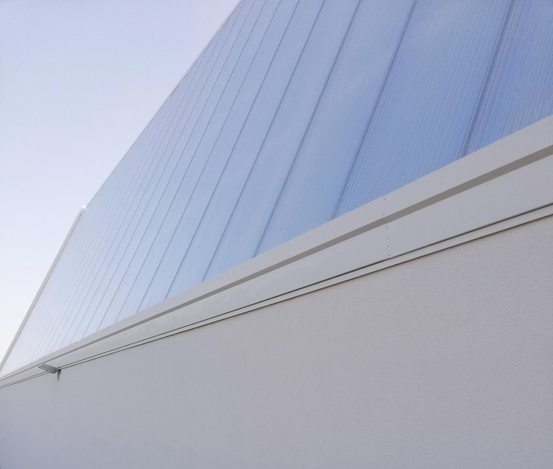 scuola materna e palestra. La palestra viene illuminata nel fronte Nord mediante l'ampia parete in policarbonato color bianco latte. Frutto di un attento studio della illuminazione naturale dell'ambiente interno.