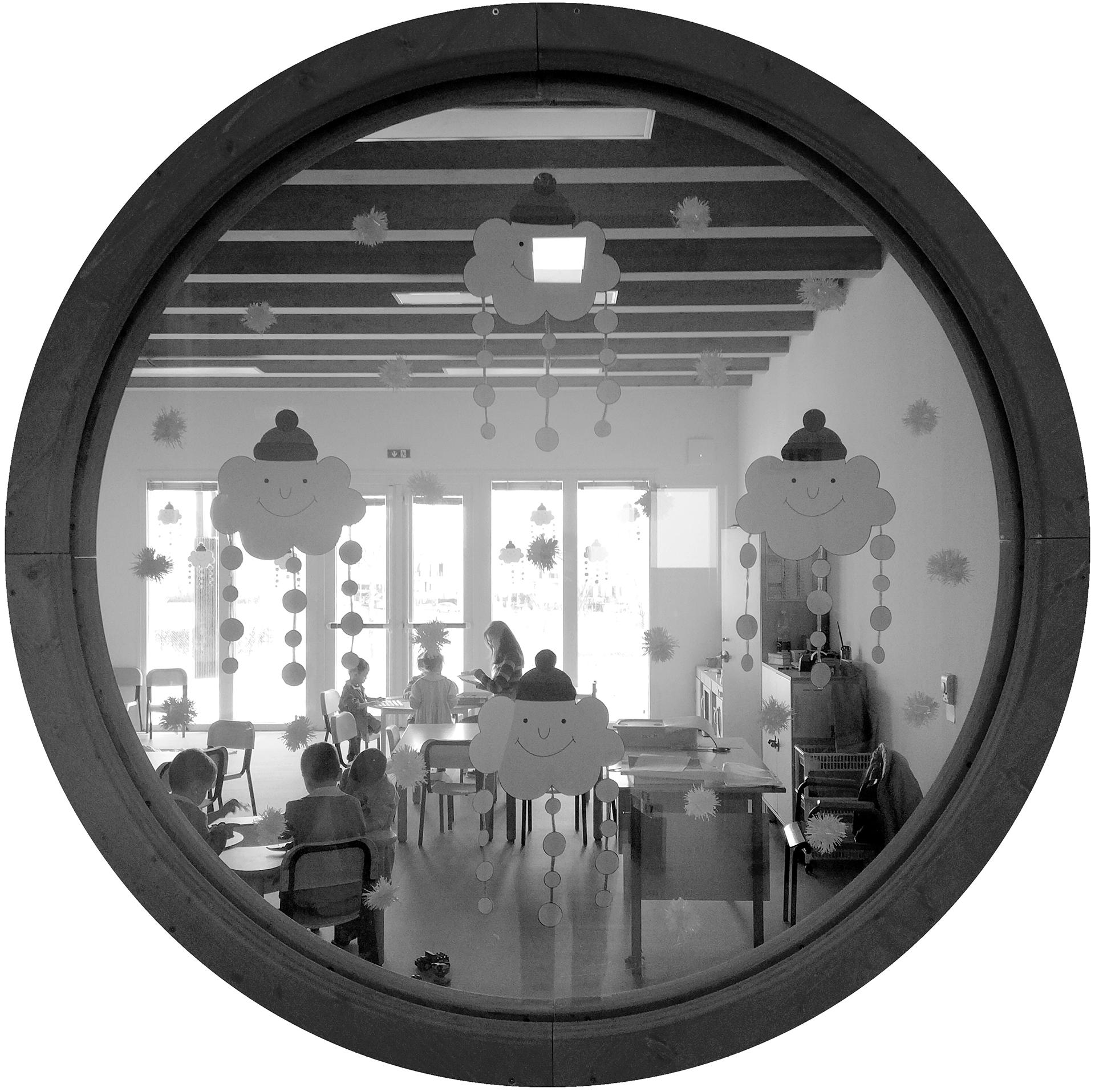 scuola materna e palestra. l'aula tipo vista dall'oblò nella zona filtro che separa ciascun aula dal disimpegno. Le aule sono caratterizzate da spazi luminosi, flessibili e molto funzionali che possono essere riadattati ad ogni esigenza.