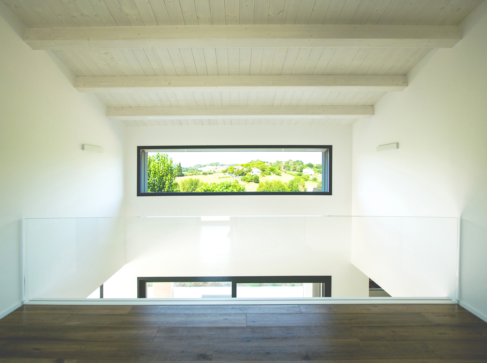 casa AI GR. dal ballatoio dove trova spazio una zona lettura ci si affaccia sulla zona giorno. In fondo l'ampia vetrata da cui si può ammirare il panorama delle campagne Jesine circostanti.