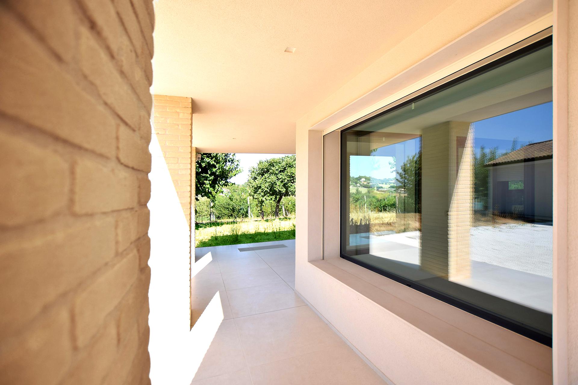 casa AI GR. il portico all'ingresso è caratterizzato da ampie finestre vetrate che garantiscono una prosecuzione del giardino anche all'interno dell'abitazione.