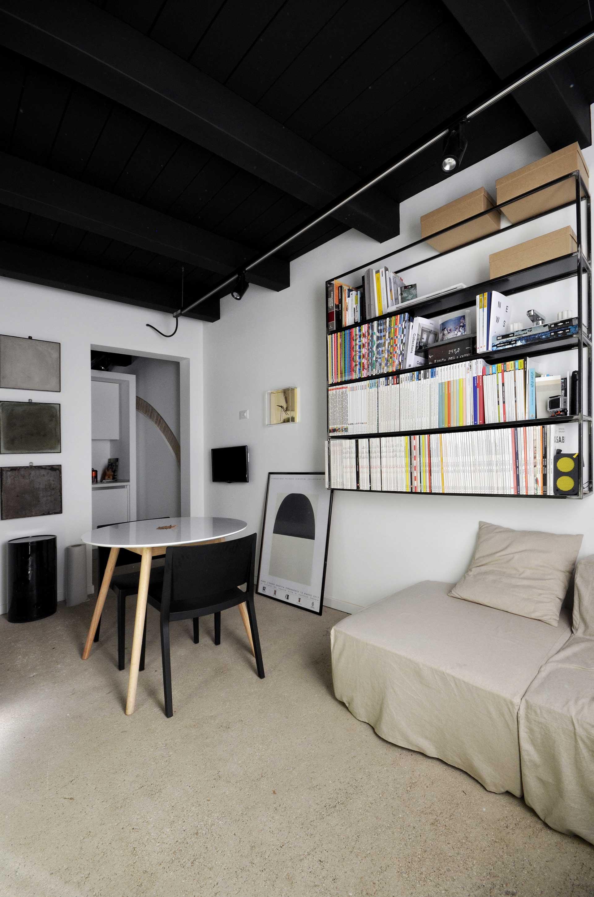 casa CM127. veduta della libreria in ferro disegnata dall'architetto Francesco Valentini e della zona divani.