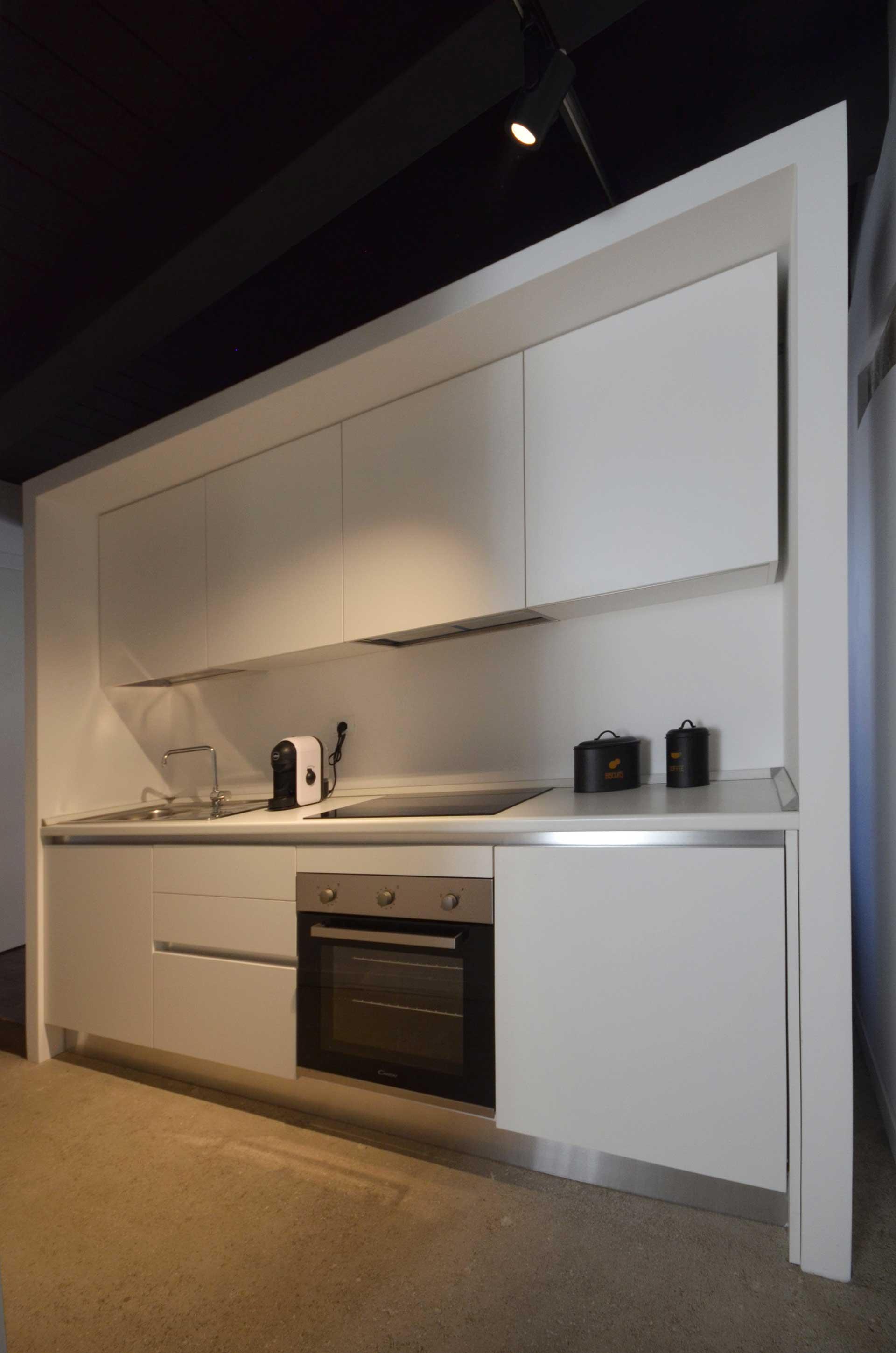 casa CM127. Veduta della zona cucina, perfettamente inserita all'interno della quinta contenitiva che separa la zona giorno dalla camera.