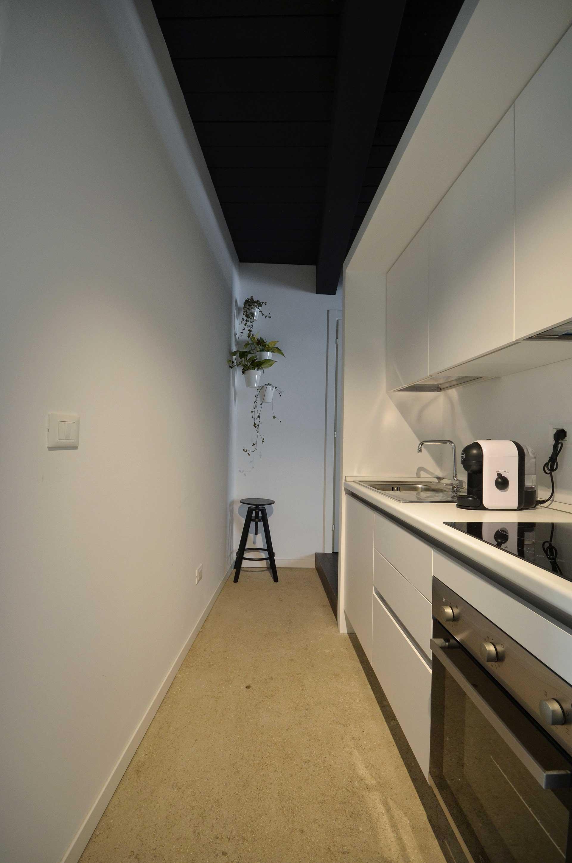 casa CM127. Veduta della cucina e sullo sfondo il verde che colora le bianche pareti minimali del piccolo appartamento.