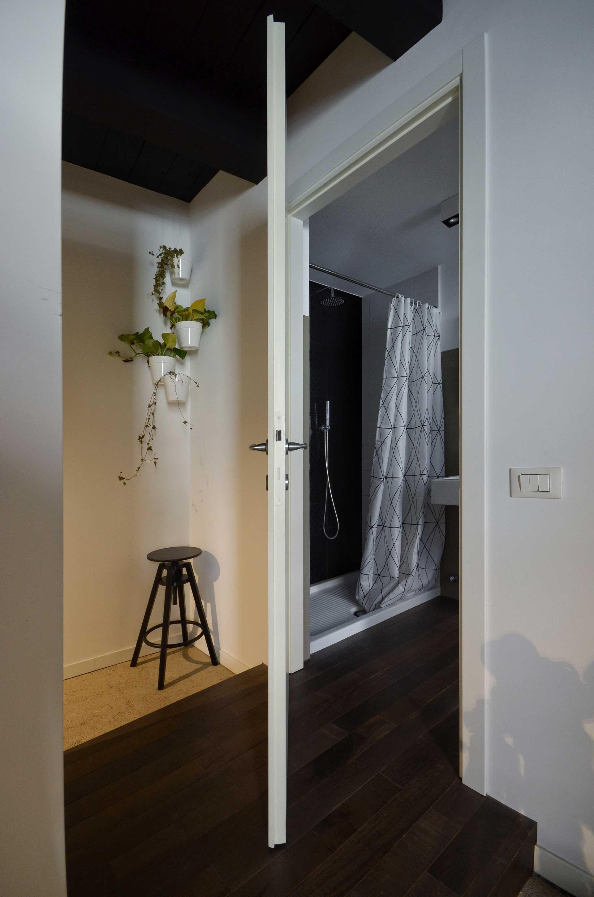 casa CM127. veduta di ingresso del bagno dalla camera. Notare pedana di rialzo rivestito in parquet della ditta Fenni.
