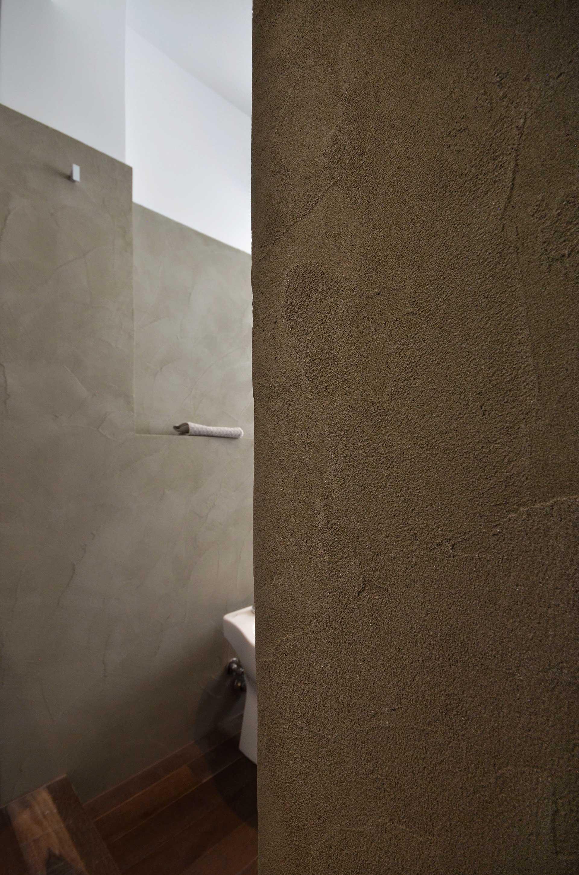 casa CM127. La matericità delle pareti del bagno. Toni caldi, neutri e naturali. Un ambiente molto rilassante.