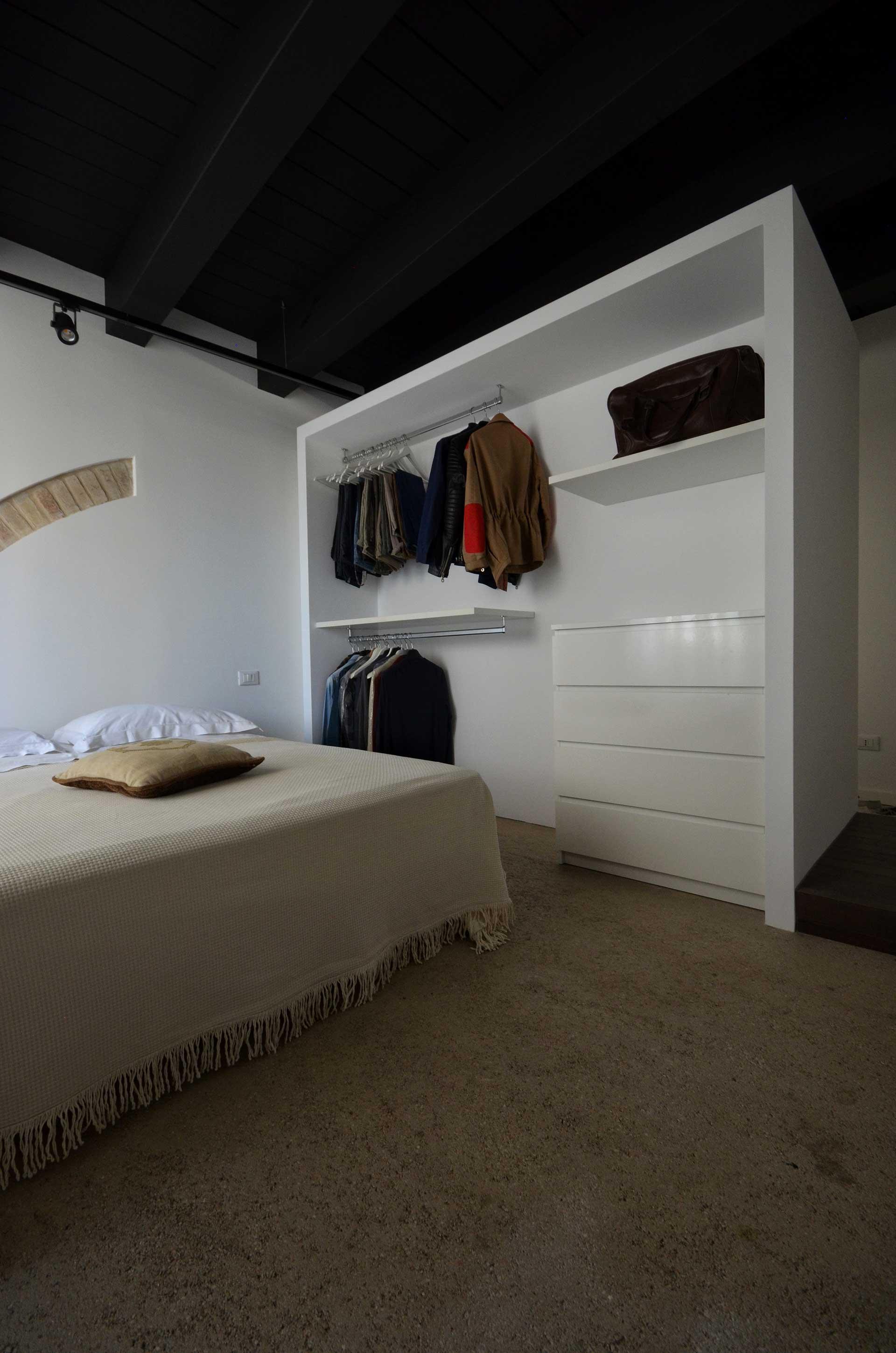 casa CM127. Vista della cabina armadio e del sistema di illuminazione che caratterizza interamente gli ambienti. Un soffitto vecchio ligneo tinteggiato nero opaco e un binario con faretti ptoiettori.