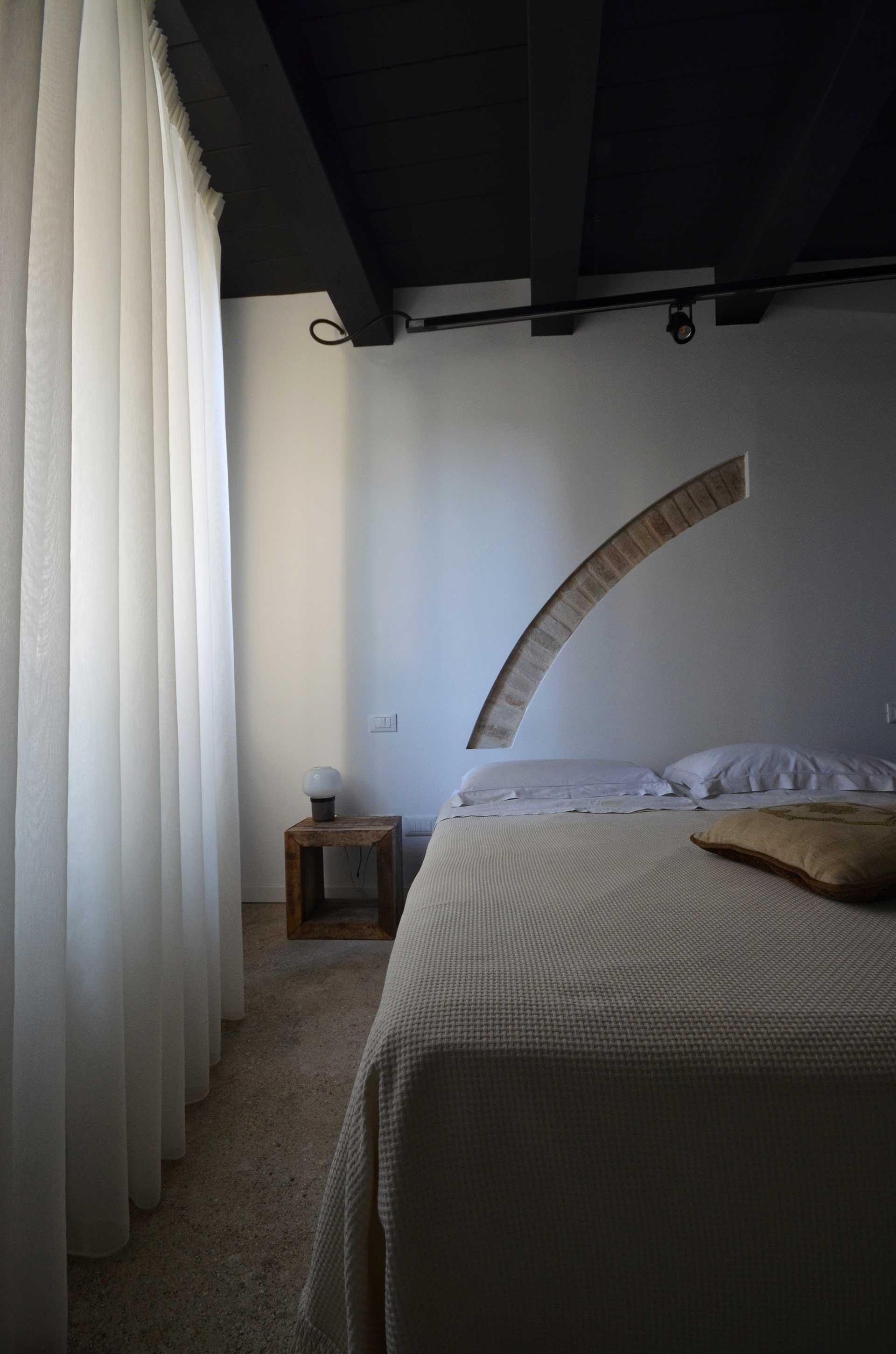 casa CM127. la testata del letto caratterizzata dalla presenza dell'antico arco che è stato trovato durante i lavori di ristrutturazione.