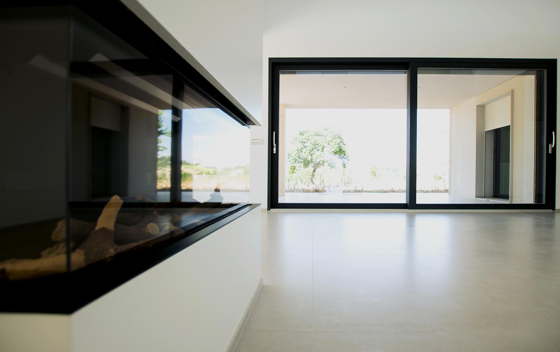 casa AI GR. il grande salone al piano terra, dove al centro si trova il camino, simbolo di focolare domestico.