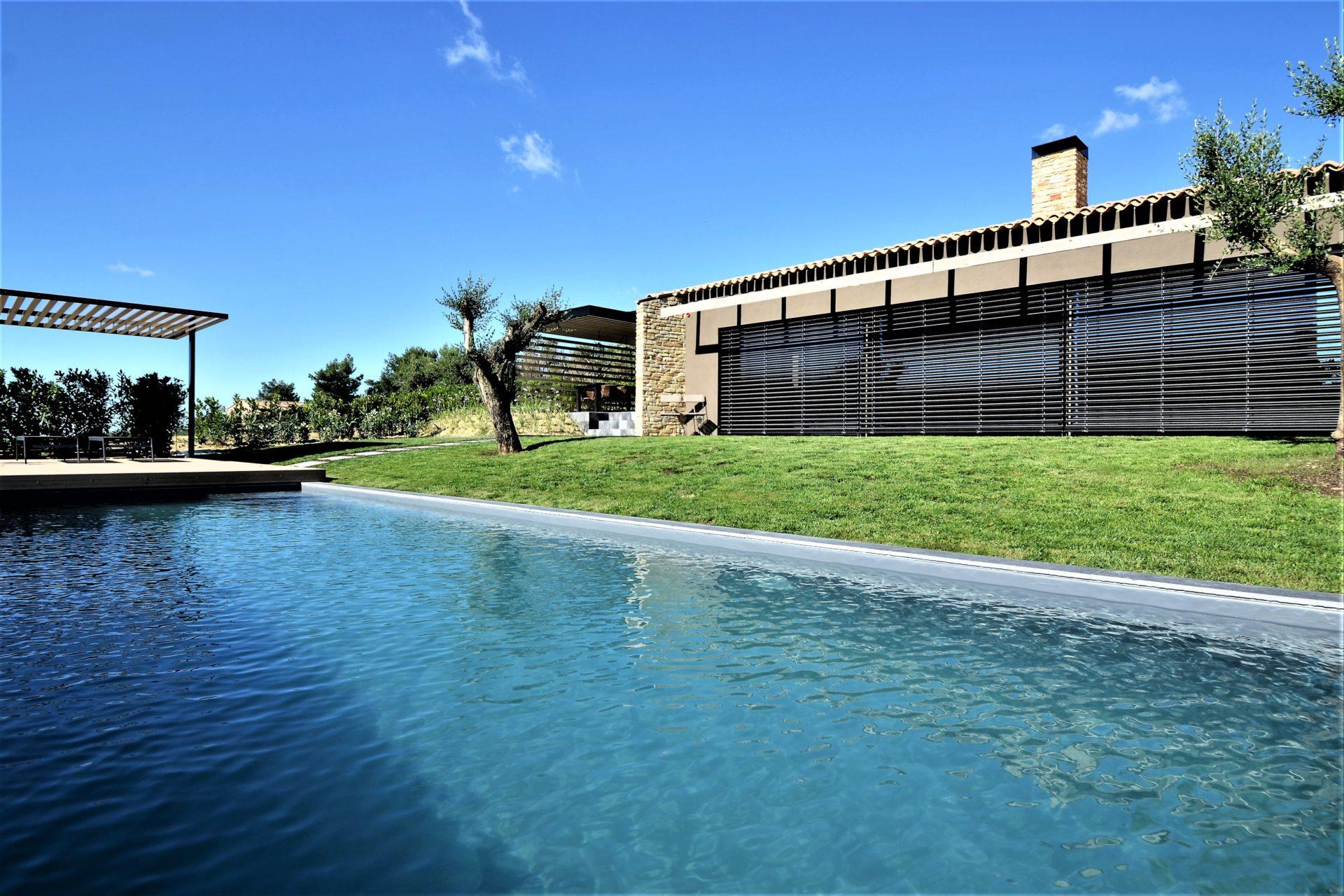 casa HR. Veduta dalla zona piscina. Sulla sinistra il telaio metallico: una cornice sul paesaggio della campagna marchigiana