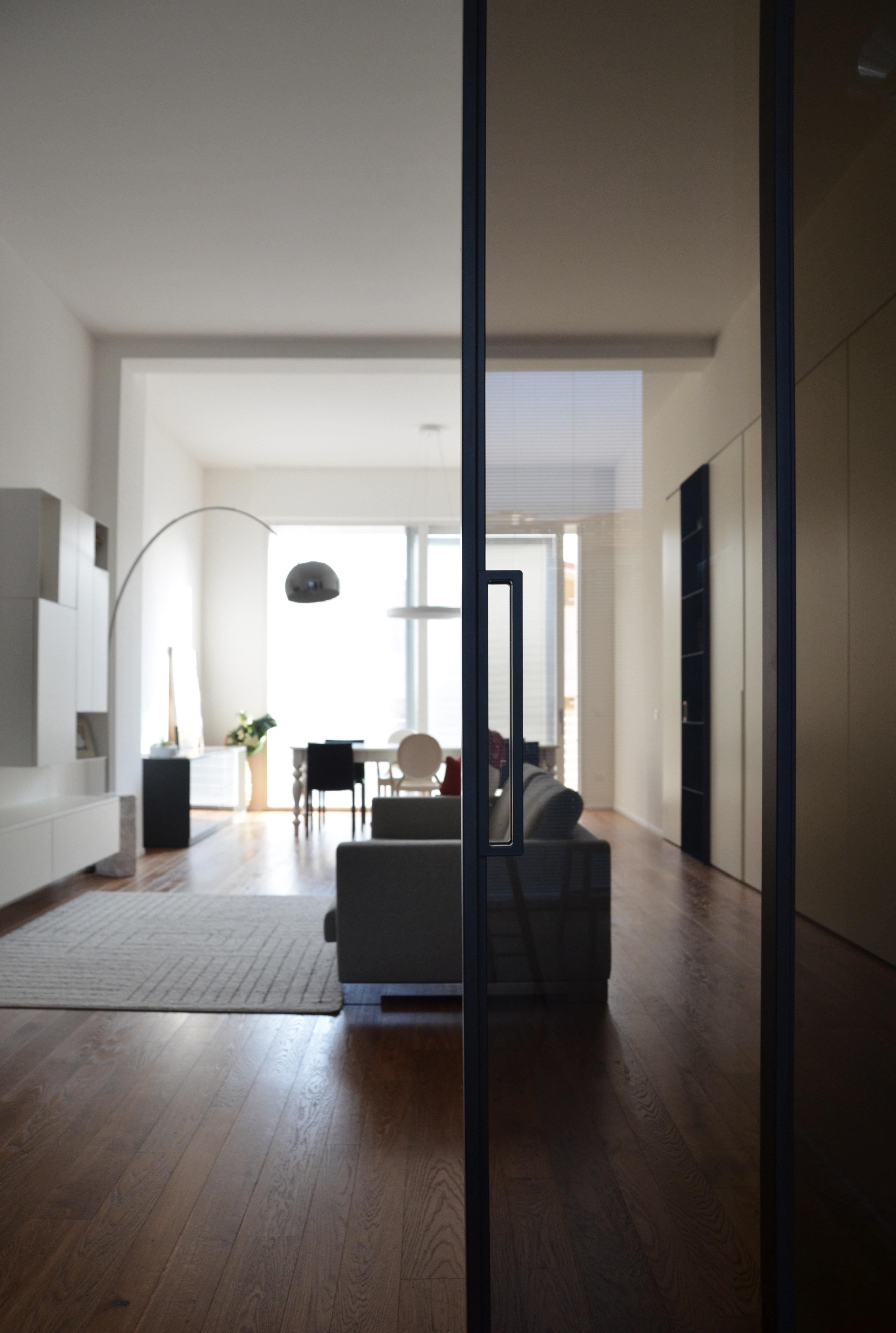 casa MB SR. dalla cucina la zona giorno, living e divani. In primo piano la porta rimadesio.