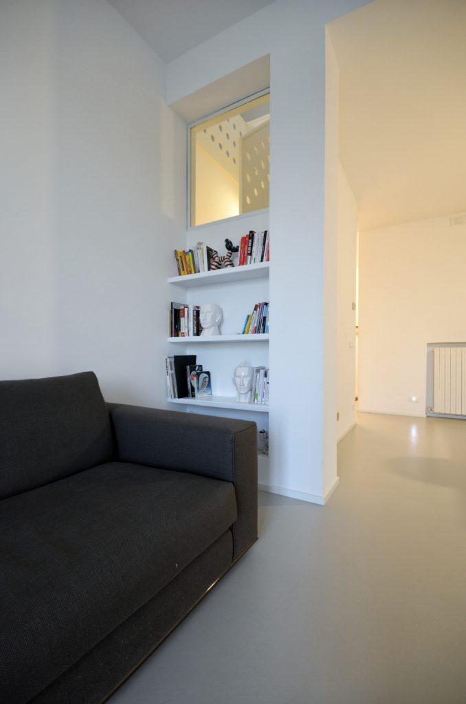 """casa SQ AA. la libreria ricavata dalla tamponatura che nasconde la scala che porta alla mansarda. Tale oggetto si concepisce anche come """"lampada""""."""